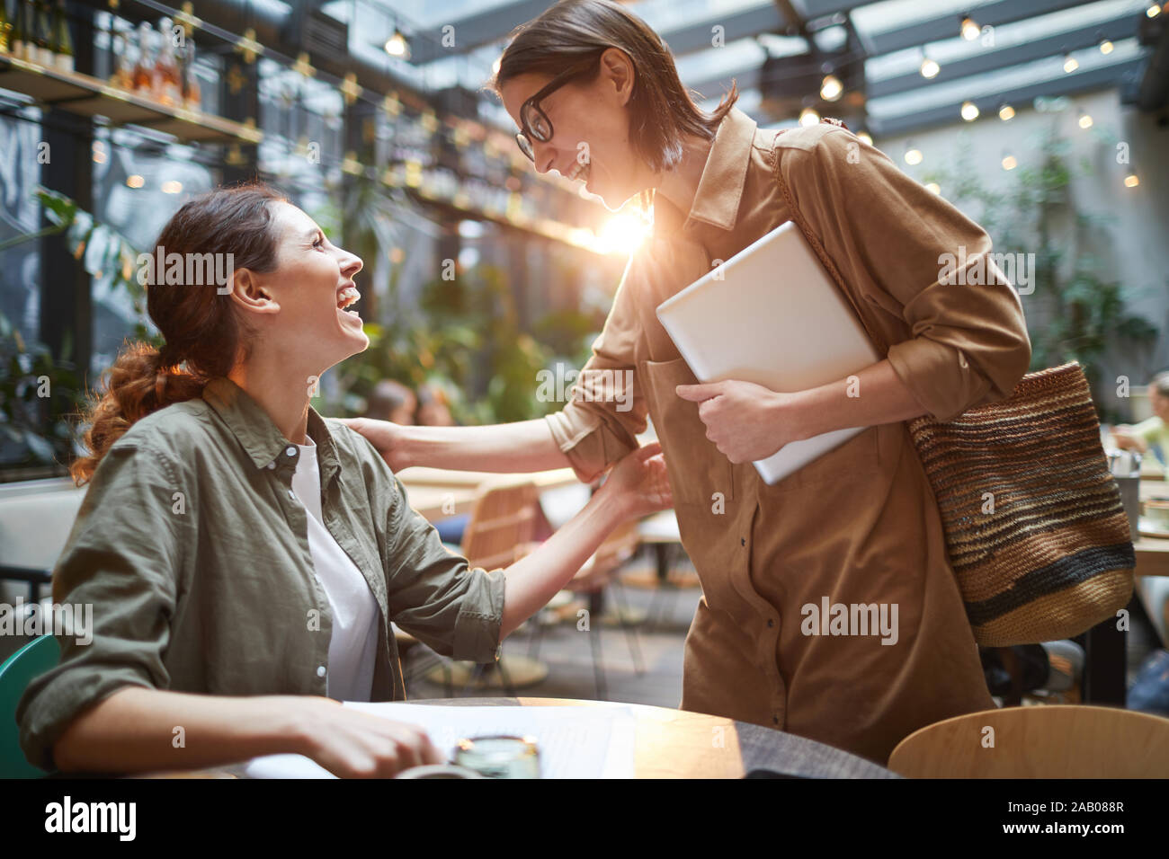Side view portrait of two young women greeting each other joyfully during meeting in cafe on outdoor terrace decorated with lights Stock Photo
