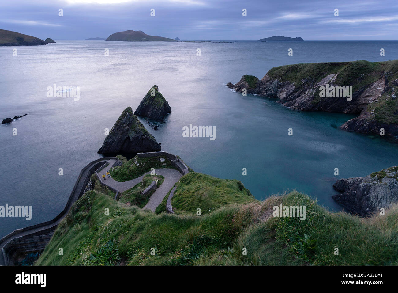 Woman and child walking uphill on windy road to Dunquin Harbor, Dunquin, County Kerry, Republic of Ireland Stock Photo