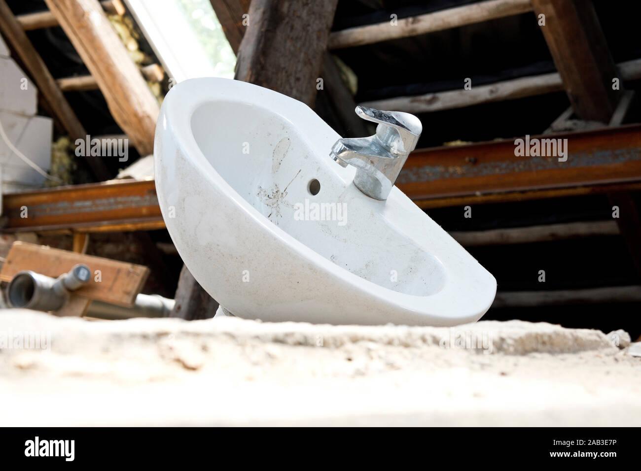 Ein Waschbecken mit Wasserhahn auf dem Fußboden in einem Abrisshaus |A sink with faucet on the floor in a demolition house| Stock Photo