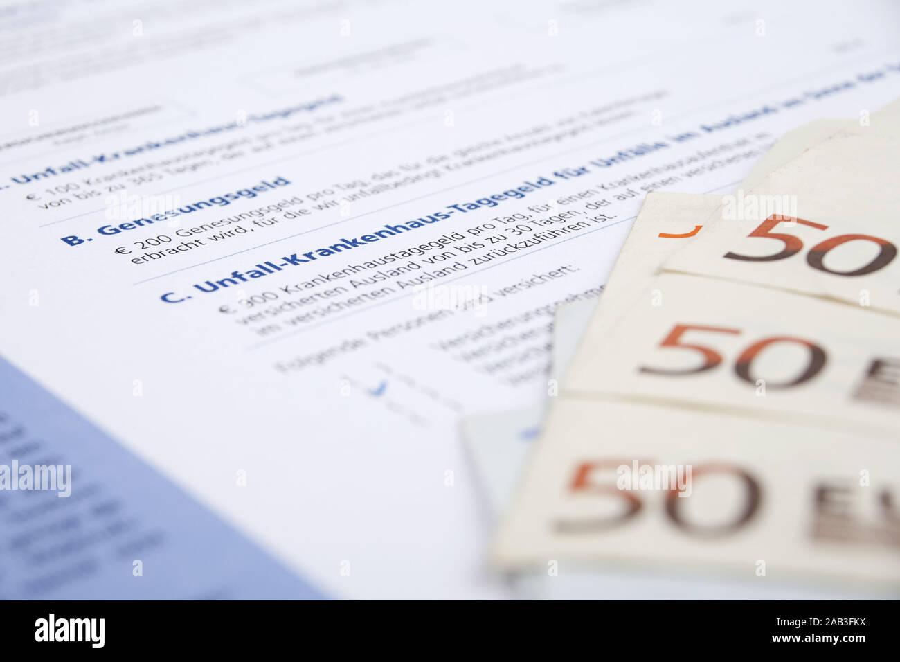 Versicherungsschein einer Unfallversicherung mit Geldscheinen  Insurance policy of accident insurance with bank notes  Stock Photo