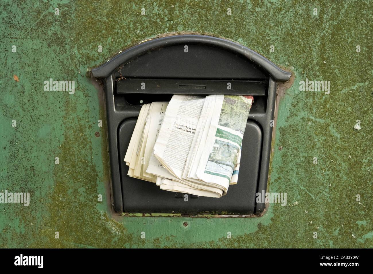 Briefkasten mit einer älteren Tageszeitung |Letterbox with an earlier newspaper| Stock Photo