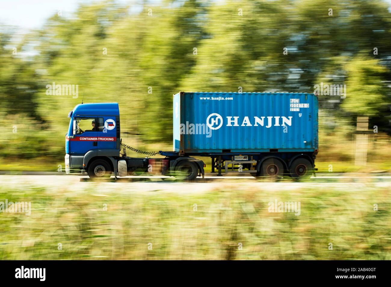 Lastkraftwagen mit einem Sattelauflieger und einem Container unterwegs in einem Gewerbegebiet |Trucks with a trailer and a container road in an indust Stock Photo