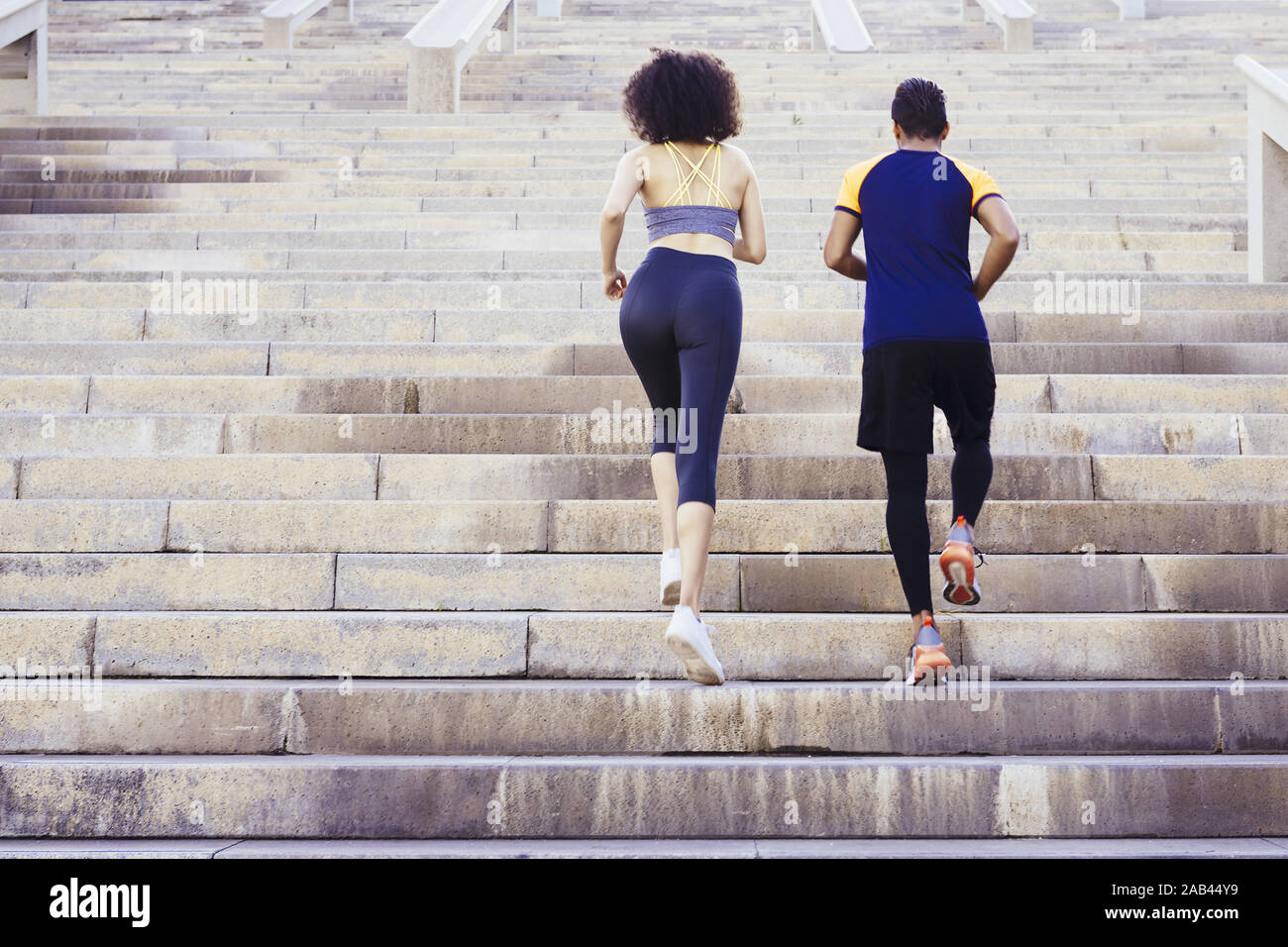 young runners couple running upstairs on city stairs, fitness, urban sports workout and healthy lifestyle concept, copy space for text Stock Photo