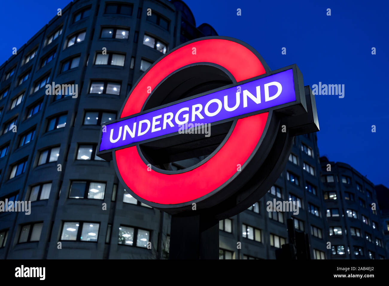 LONDON - NOVEMBER 20, 2019: London Underground tube red logo sign train station at night Stock Photo