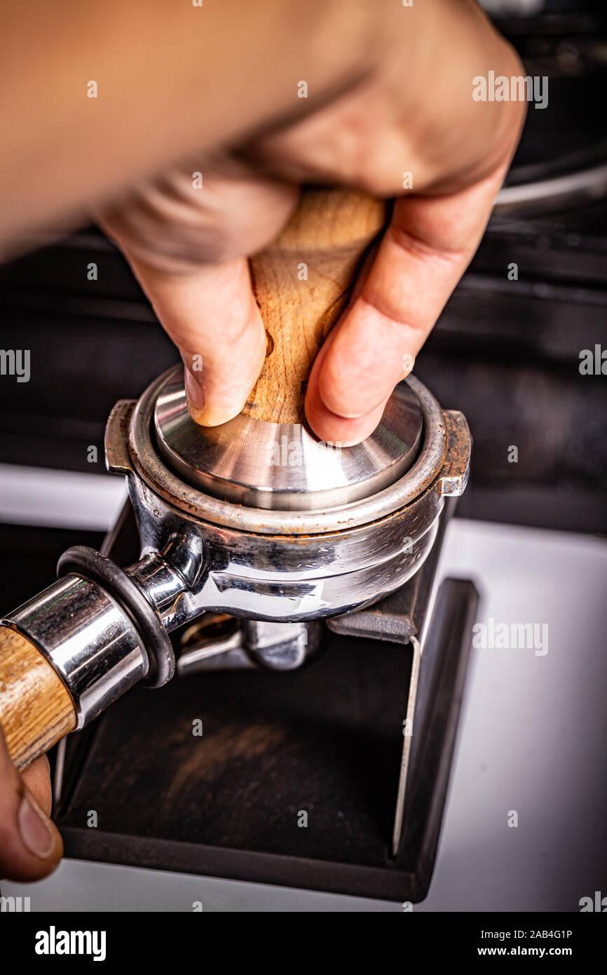 Barista presses ground coffee using tamper. Stock Photo