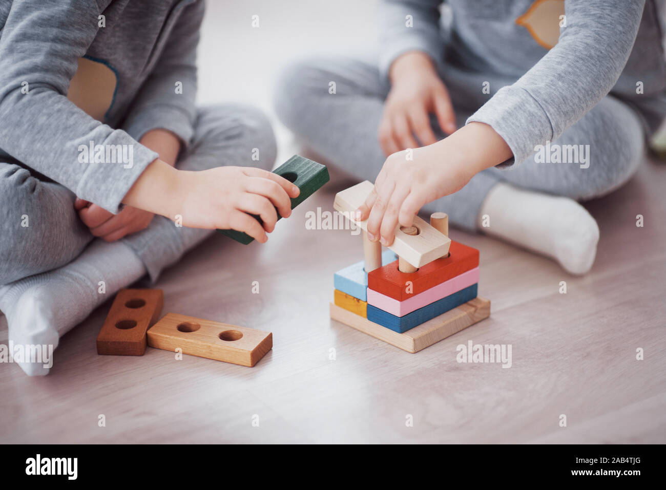 Children play with a toy designer on the floor of the children's room. Two kids playing with colorful blocks. Kindergarten educational games Stock Photo
