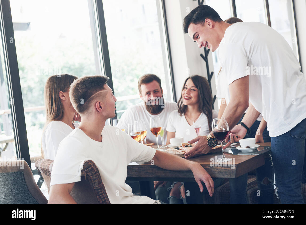 Tasty pizza on the table, with a group of young smiling people resting in the pub Stock Photo