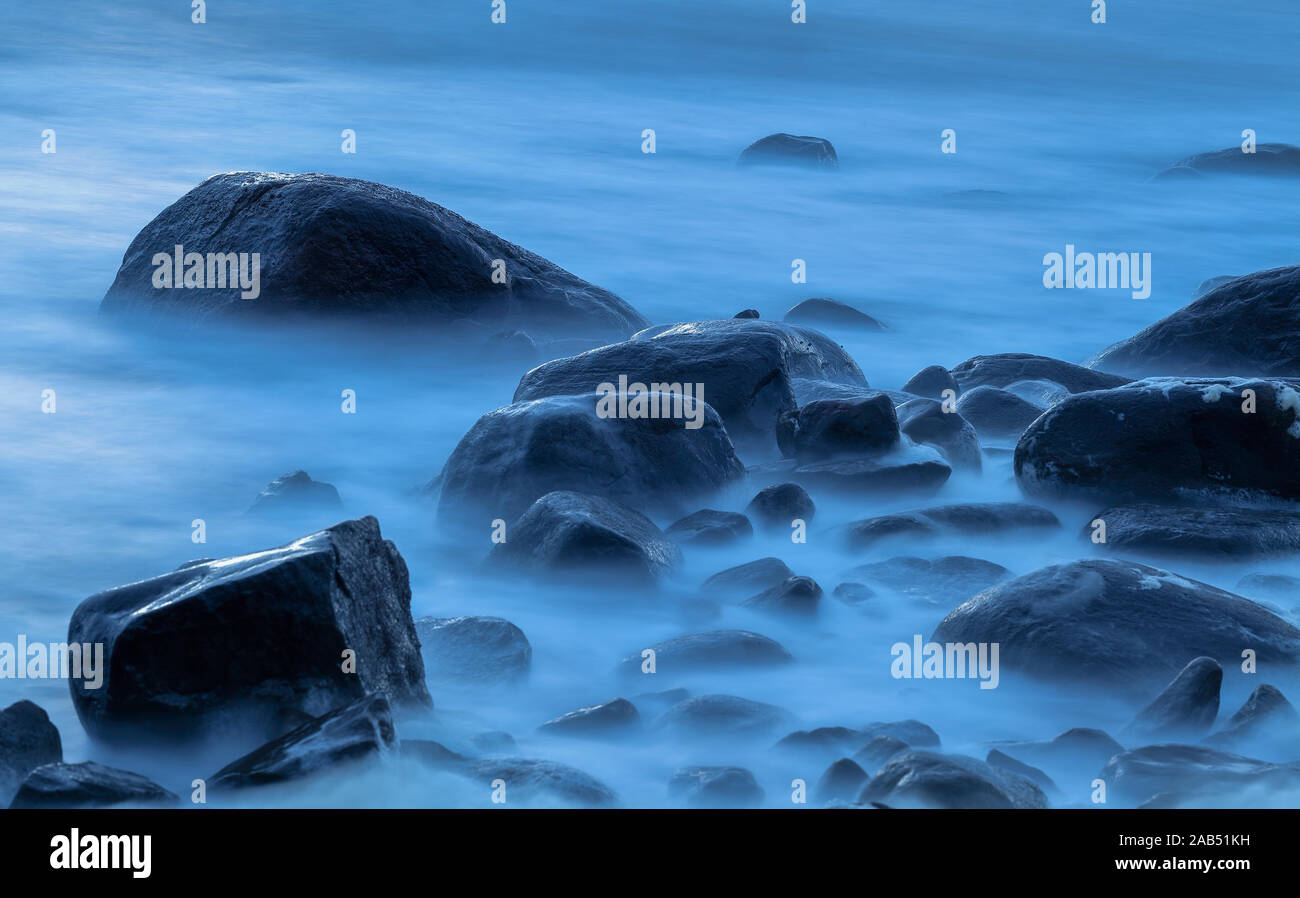 Stones in the water on a cold and windy summer night with blue light Stock Photo