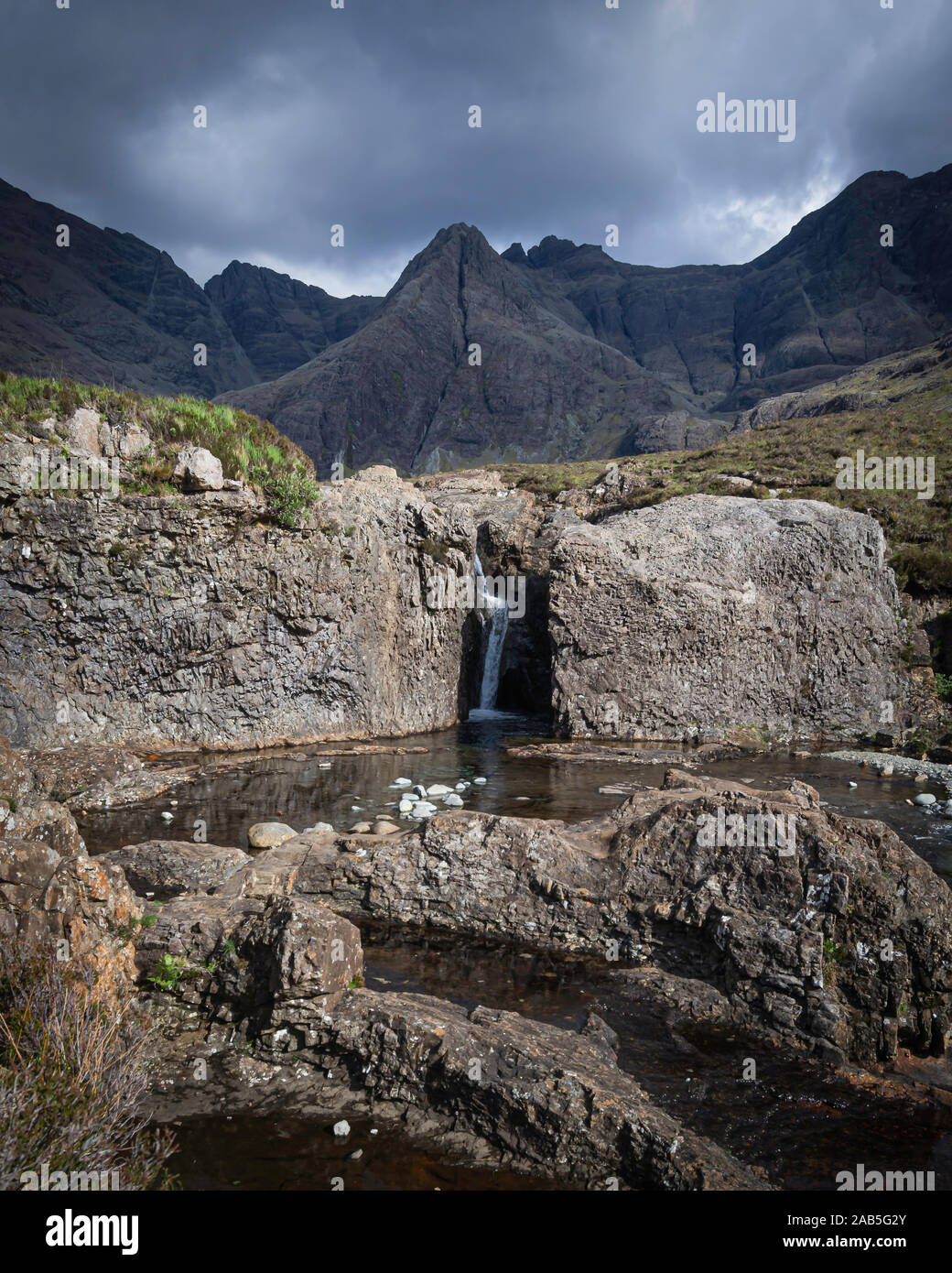 Moody sky above mountain range and small waterfall in rocky terrain in foreground.Fairy pools on Isle of Skye, Scotland,UK.Popular tourists attraction. Stock Photo
