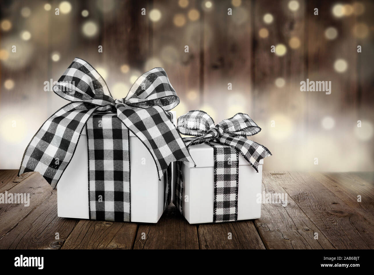 rustic christmas gifts with black and white buffalo plaid check ribbon side view with a dark wood and twinkling light background 2AB6BJT