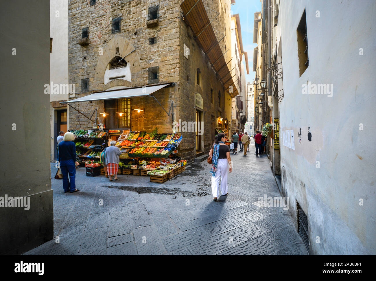 Italians pass by a fresh produce market near a narrow alley away from the main tourist areas in Florence, Italy Stock Photo