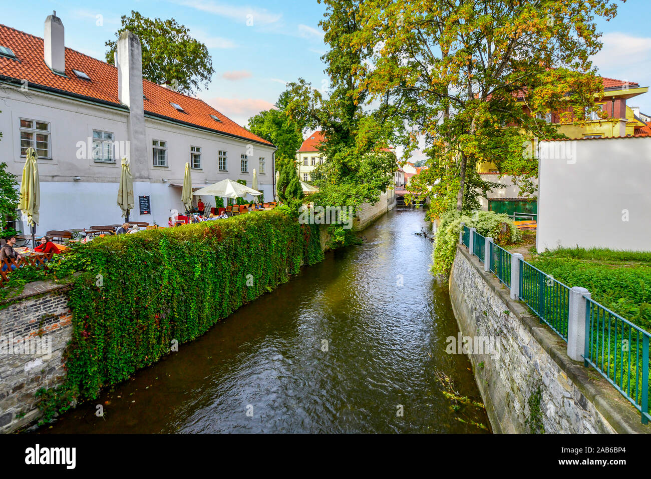 Tourists and locals dine at an outdoor cafe alongside a canal just off the river Vltava in the scenic area of Kampa Island in Prague, Czech Republic Stock Photo