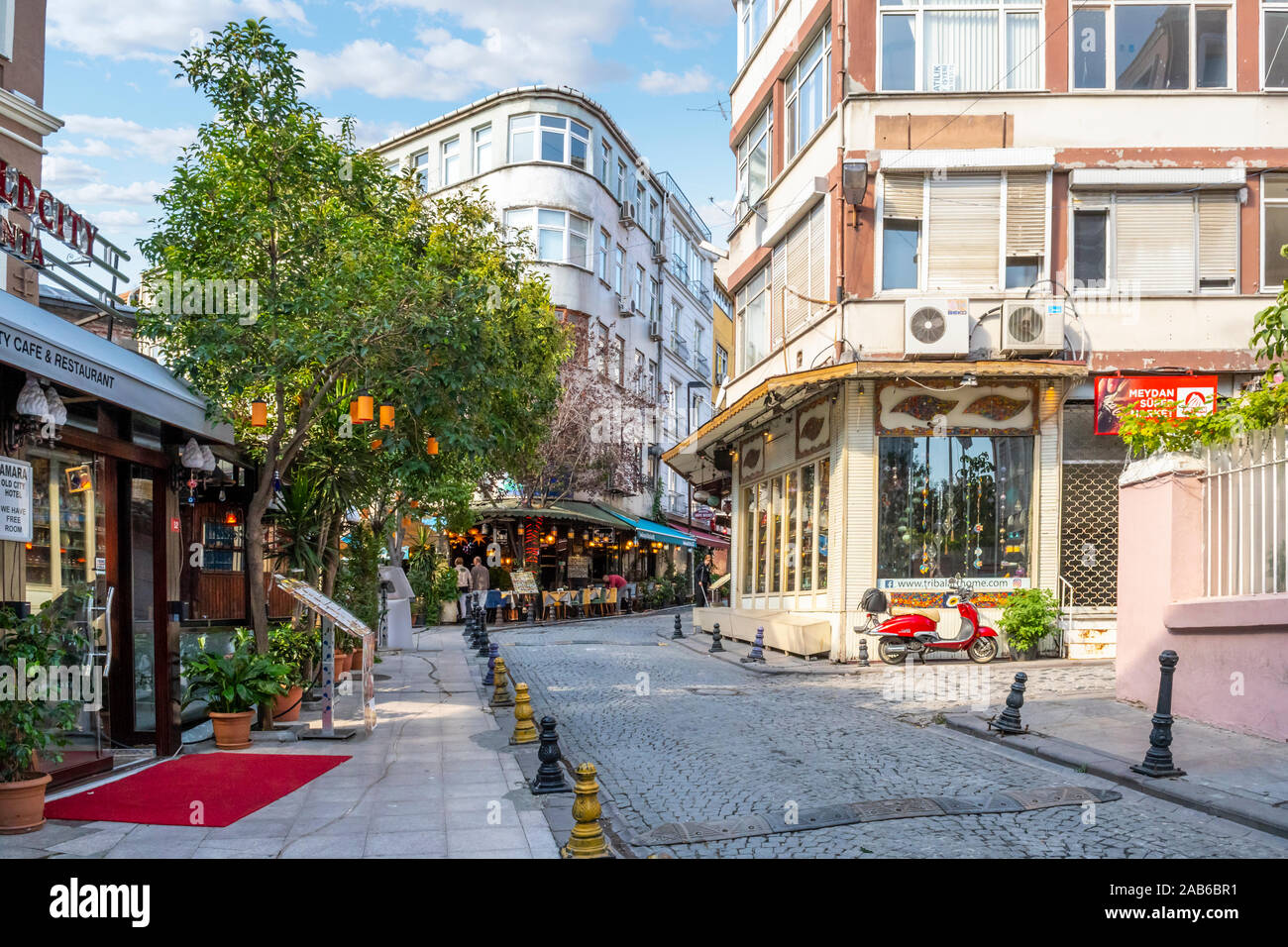 A street of cafes and shops with a motor scooter parked in a touristic section of Sultanahmet in Istanbul, Turkey Stock Photo