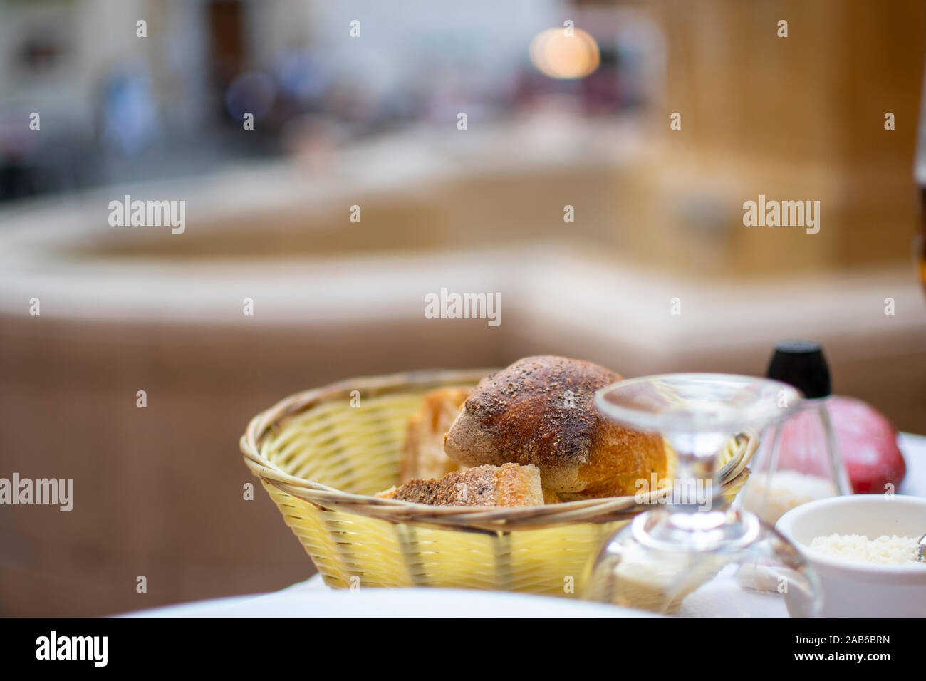 A basket of bread and rolls on a patio table in a piazza in front of a fountain in Nice France. Stock Photo