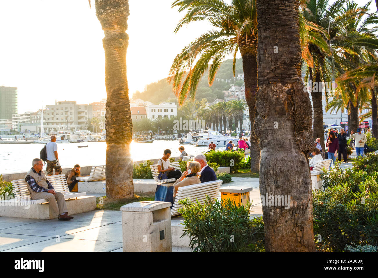 Afternoon at the Riva Promenade at the harbor of Split Croatia as tourists enjoy watching boats at sea and relax under the palm trees. Stock Photo