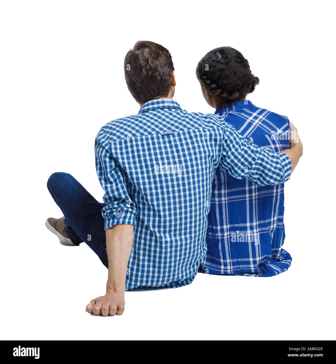 Back view of a multiethnic young couple sitting on the ground and hugging. Rear view people collection. backside view of person. Isolated over white b Stock Photo
