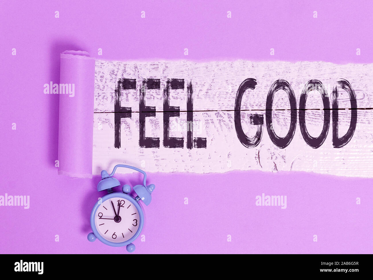 Word writing text Feel Good. Business photo showcasing relating to or promoting an often specious sense of satisfaction Alarm clock and torn cardboard Stock Photo