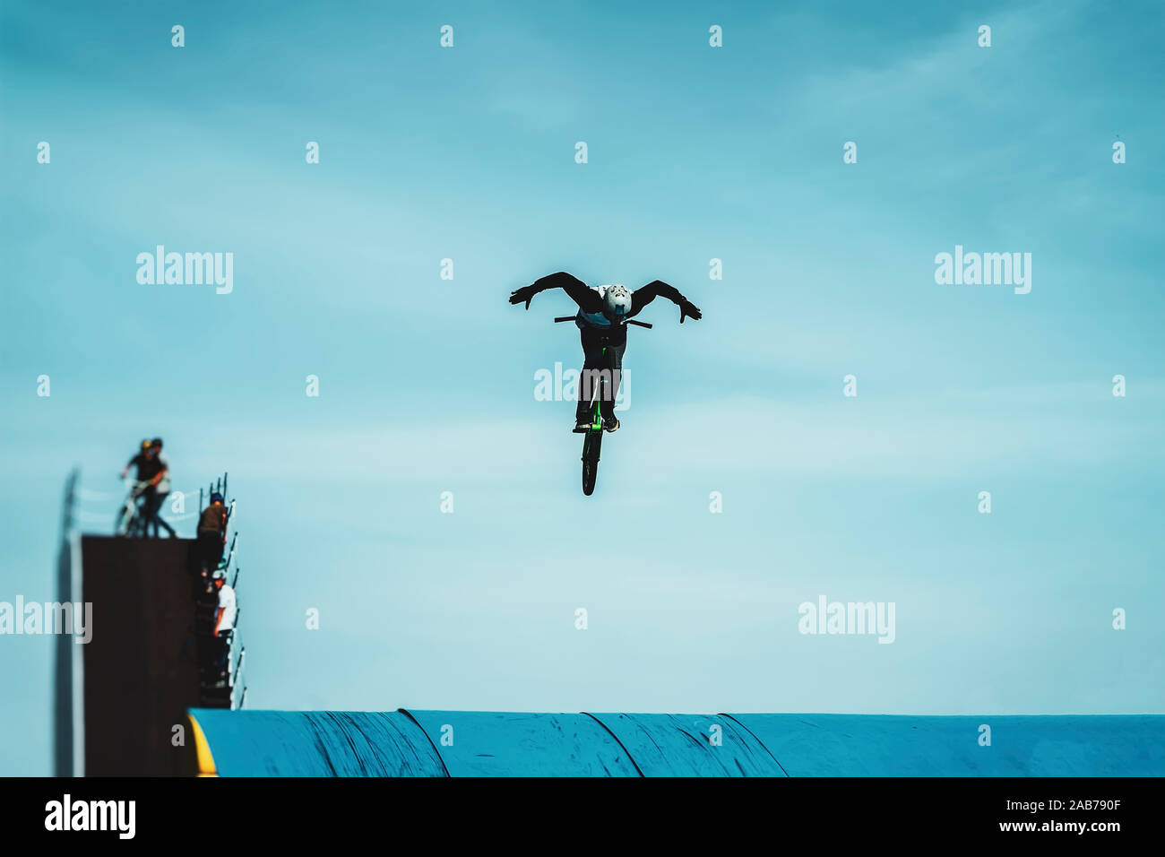 Silhouette of a unrecognizable young bike rider performing aerial BMX trick against blue sky. Extreme sport, youth culture Stock Photo