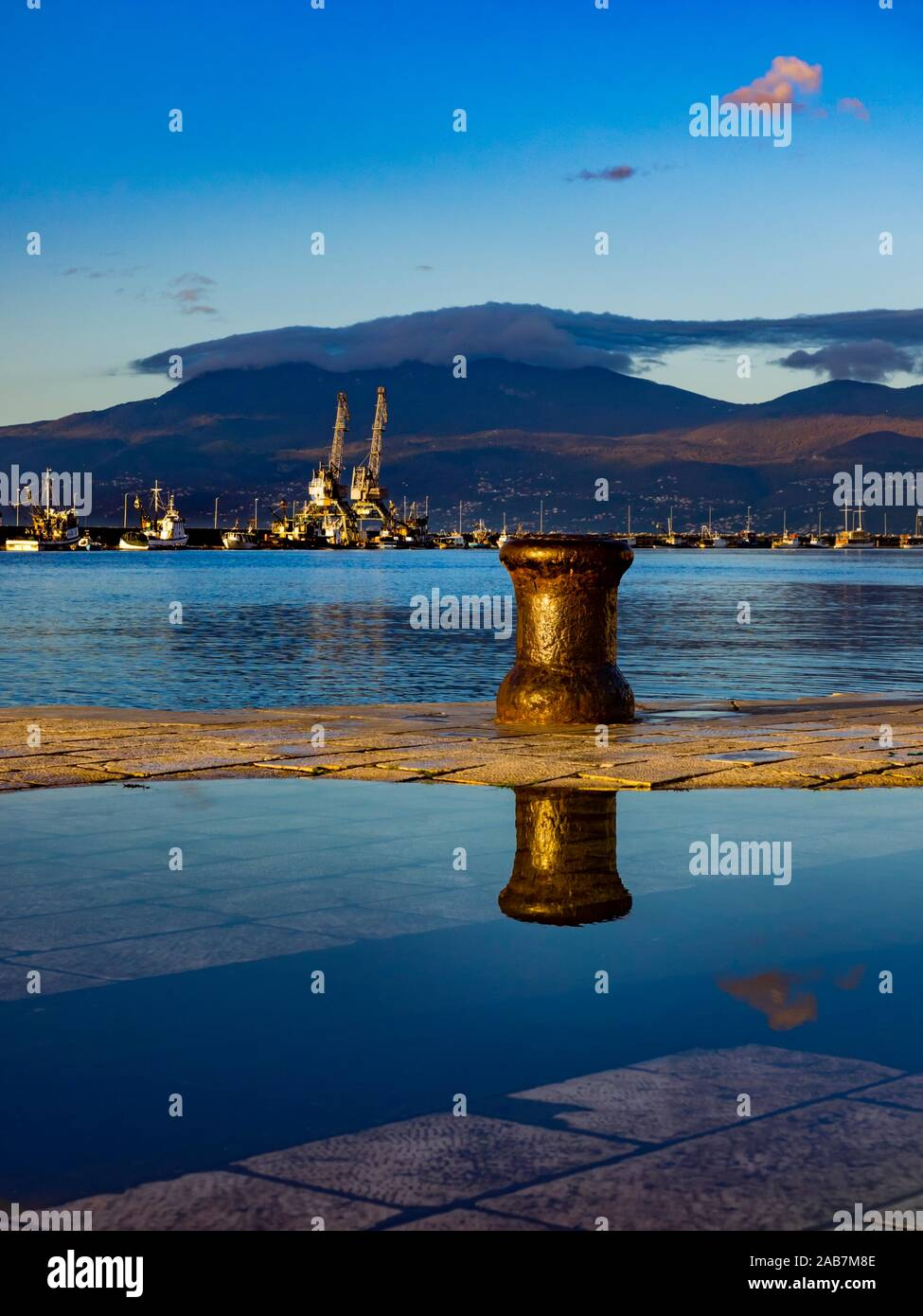 One single lonesome bollard  in harbor town Rijeka in Croatia Ucka mountain in background Stock Photo