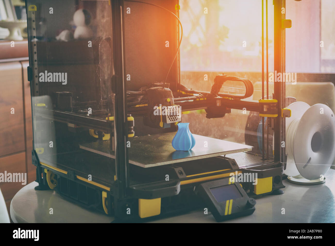 Modern 3d printer with printed three dimentional model of vase at home, nearby spool of filament Stock Photo