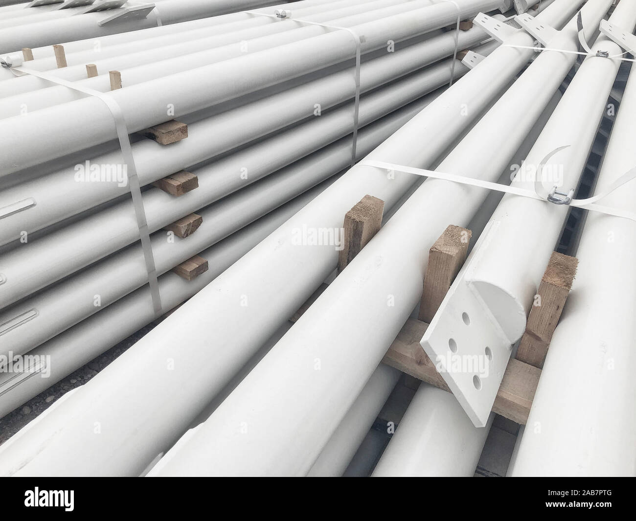 White colored stacked metal diagonal bracings with holes for bolts. Stacked metal parts of a pre-fabricated building. Fast-built camp construction par Stock Photo