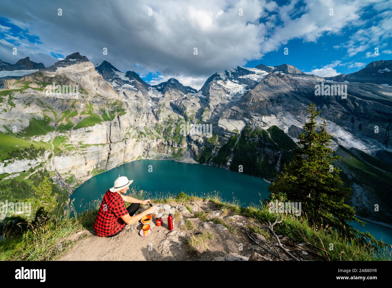 Hiker cooking food on camping stove high up above Oeschinensee lake, Bernese Oberland, Kandersteg, Canton of Bern, Switzerland, Europe Stock Photo