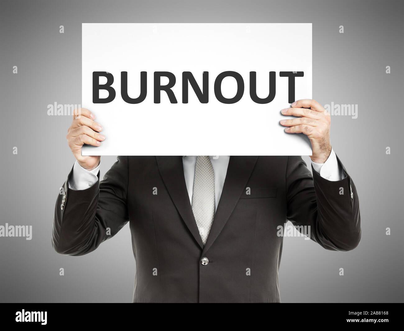 """Ein Geschaeftsmann, der ein Schild mit den Worten """"Burnout"""" in der Hand haelt Stock Photo"""