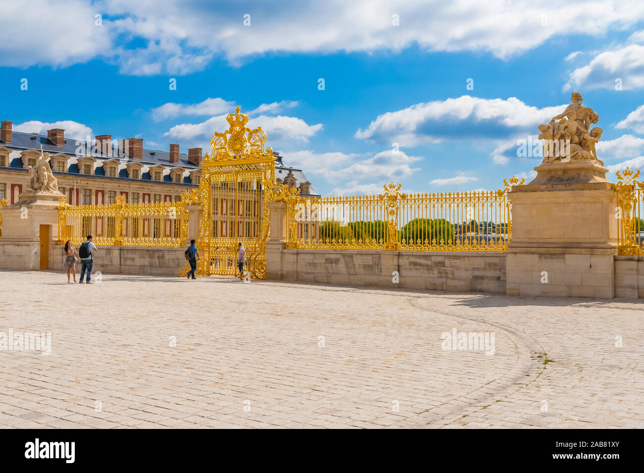Great panoramic view of the shiny golden Royal Gate, an elaborate gold leaf gate, seen from inside the Cour Royale of the famous Palace of Versailles... Stock Photo