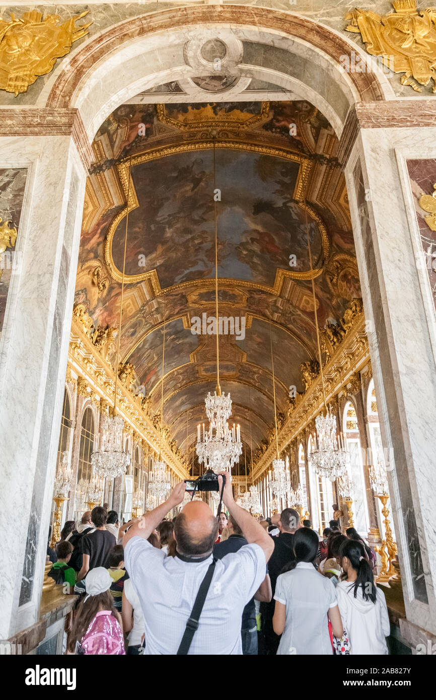 Great portrait view of a man in the War Room standing at the arched entrance of the famous Hall of Mirrors and taking photos of the beautiful painted... Stock Photo