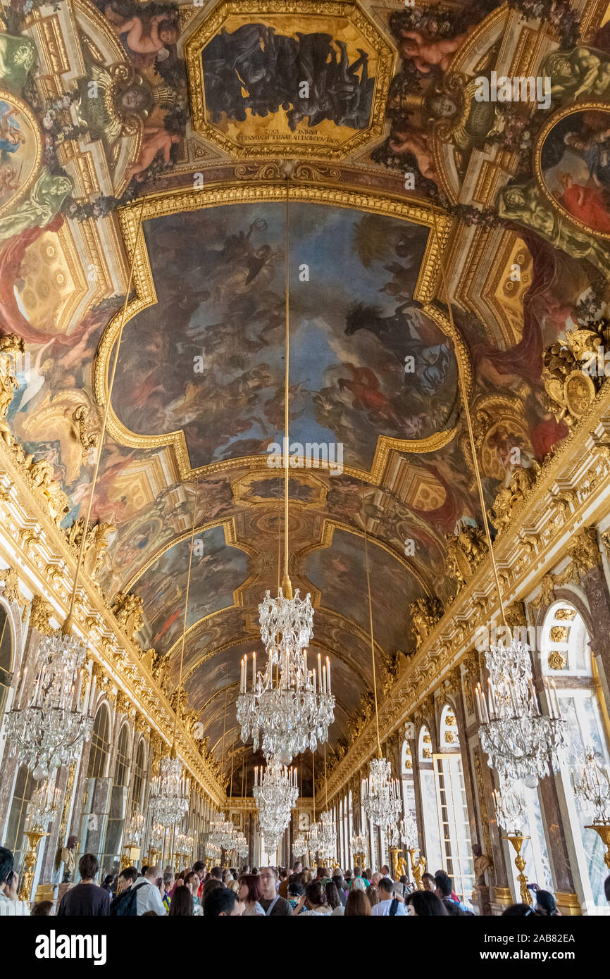 Great portrait low angle view of the Hall of Mirrors in the Palace of Versailles. The crowd of visitors admire the crystal chandeliers, gilded... Stock Photo