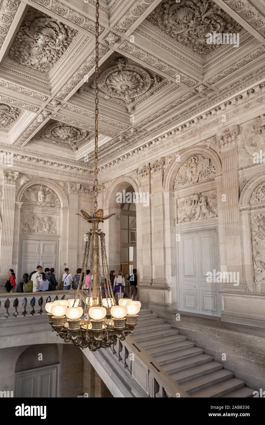 Great portrait view of a big chandelier hanging from a lovely coffered ceiling in the staircase of the famous Palace of Versailles. The decorative... Stock Photo