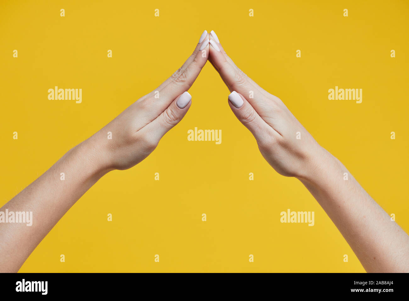 House made of woman hands isolated on yellow background Stock Photo