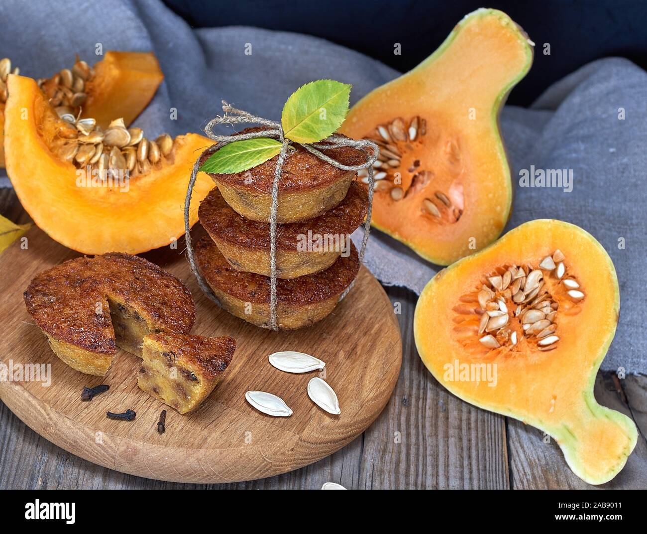 stack of muffins with a pumpkin on a round wooden board and fresh pieces of pumpkin. Stock Photo