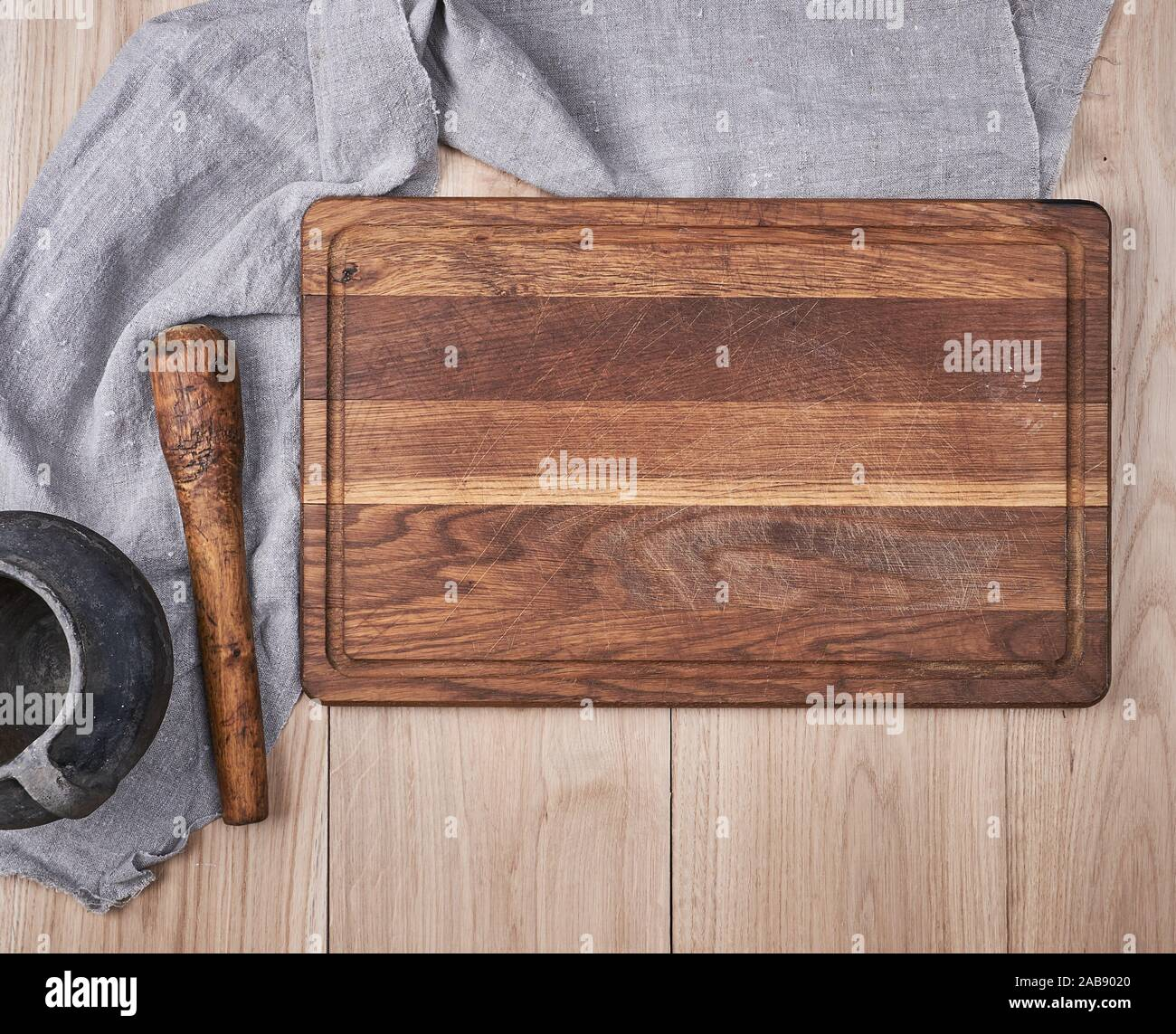 Empty old wooden kitchen cutting board and a gray towel on a table ...
