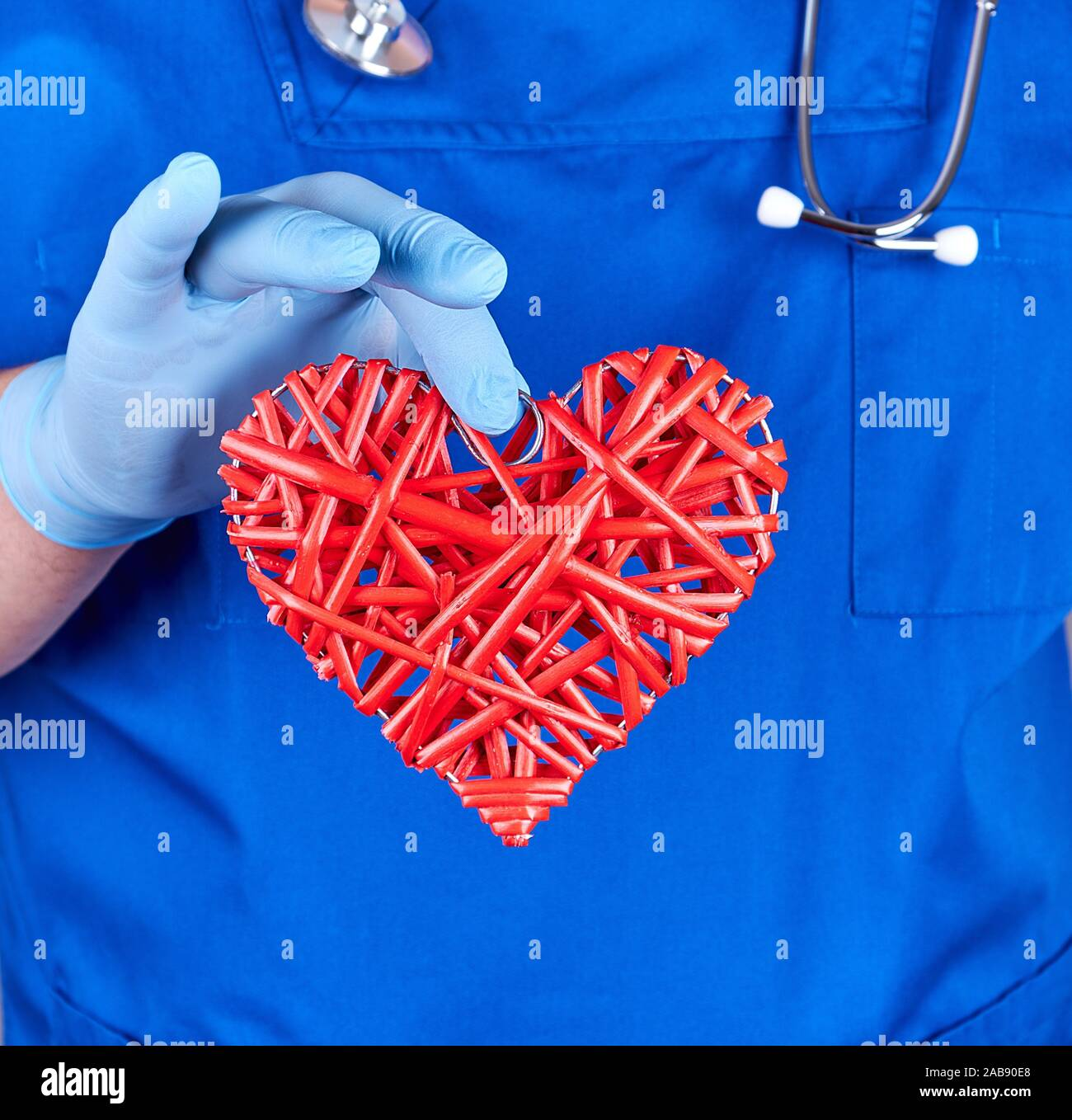 doctor in blue uniform and sterile latex gloves holds a big red heart, close up. - Stock Photo