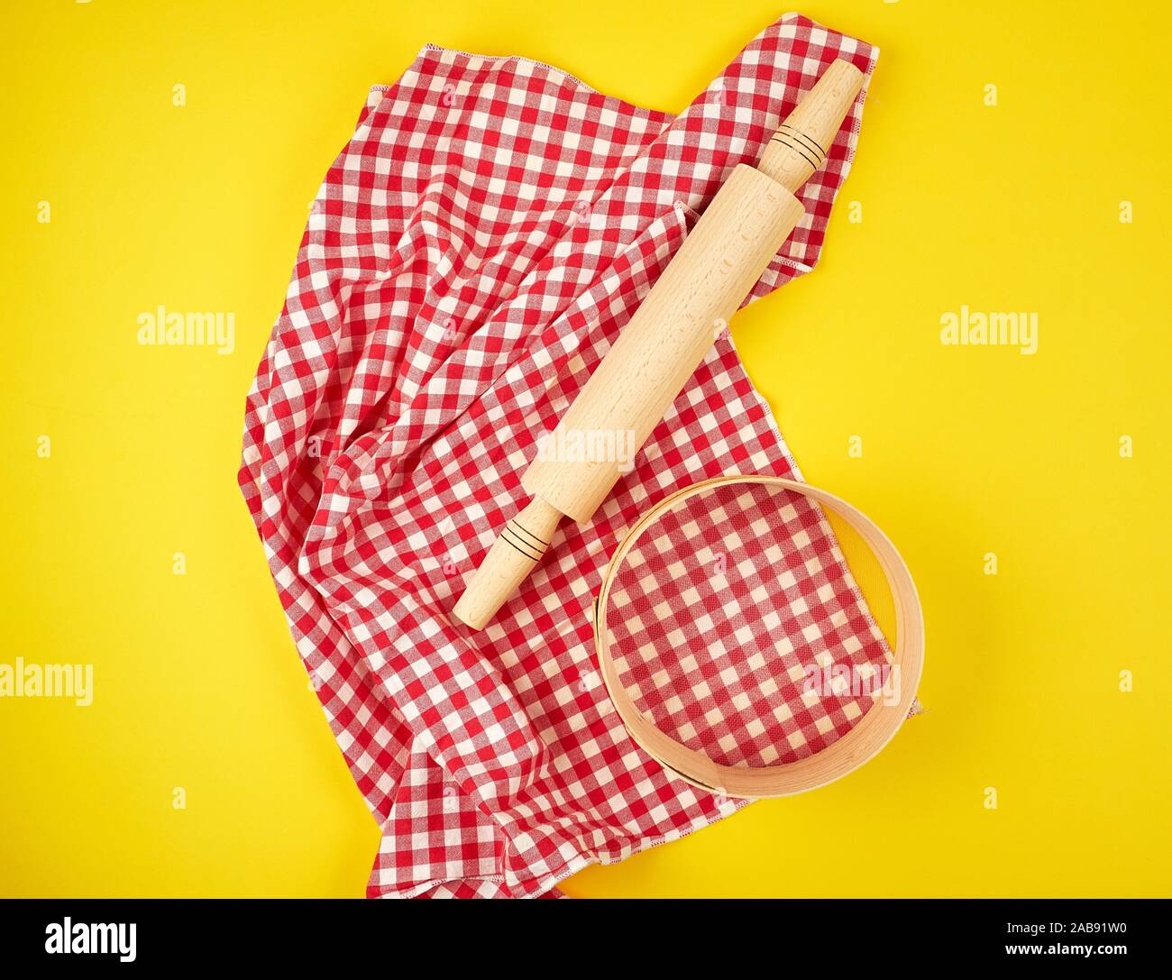 new wooden rolling pin on a red textile napkin and a round sieve for flour, yellow background, top view. Stock Photo
