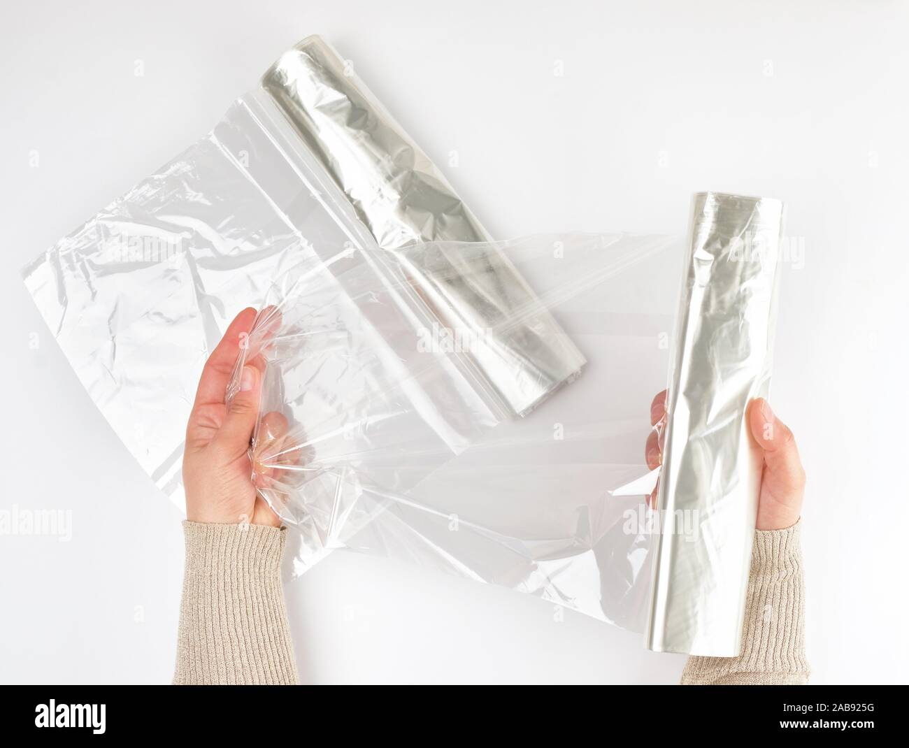 Plastic food wrap for baking products in the oven in women's hand, view from the top, white background. Stock Photo