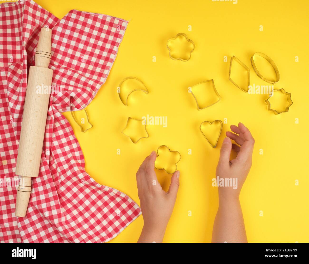 new wooden rolling pin on a red textile napkin and two female hands, yellow background, top view. Stock Photo