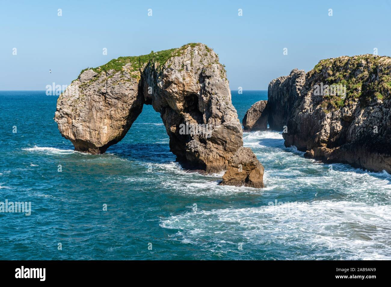 Scenic view of waves splashing against the rocky coast against blue sky. Castro de las Gaviotas, Fort of the Seagulls, and Beach of the Huelga, Stock Photo