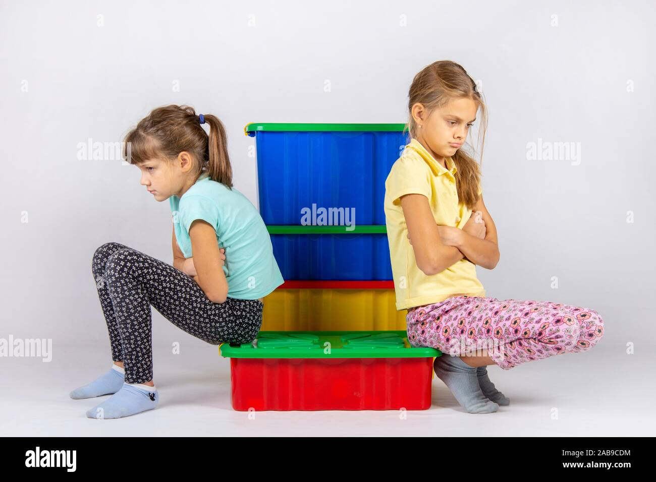 Two girls quarreled, sit on a box and turned away from each other. Stock Photo