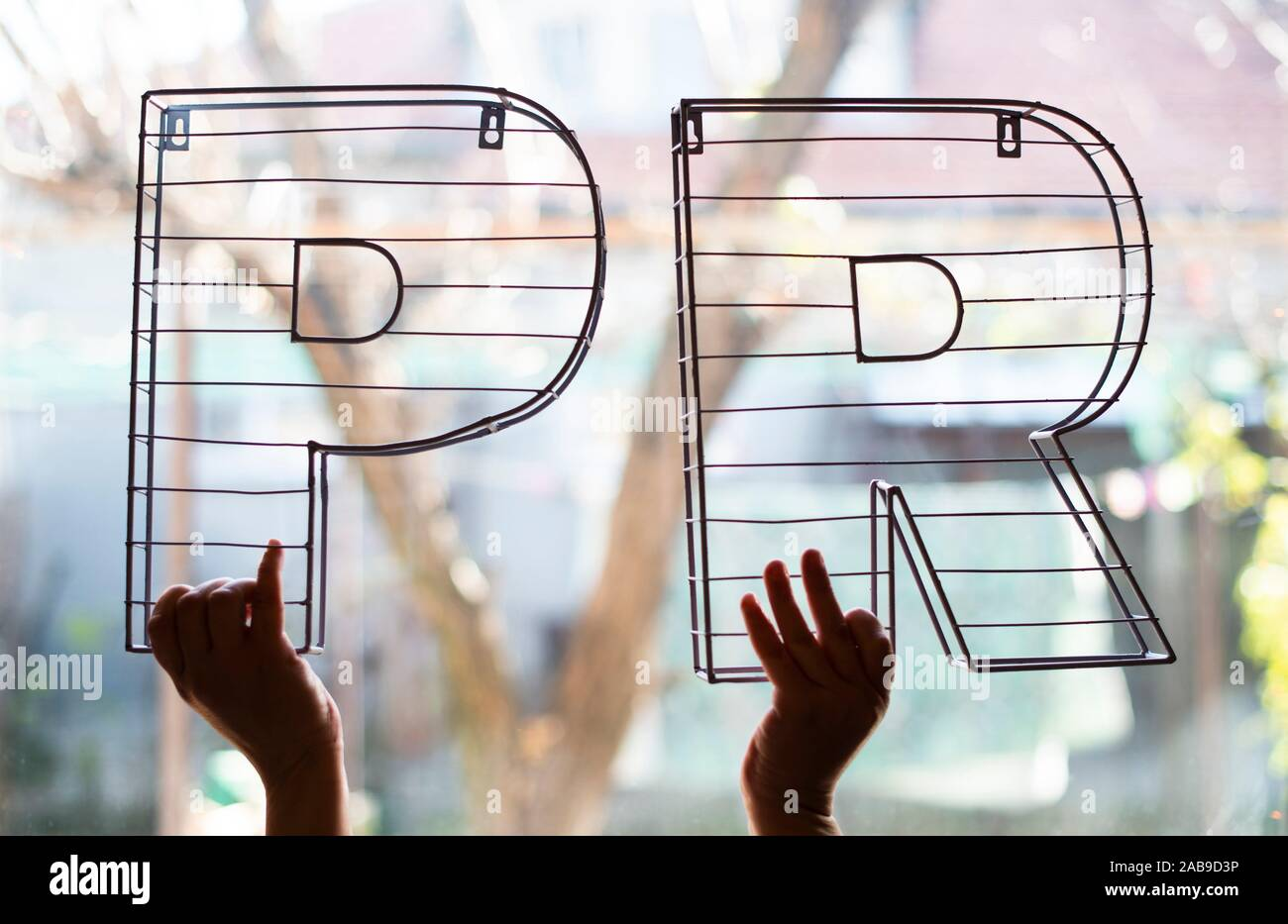 Public Relations letters in front of the window. Hands hold 3D metal letters on backlight. Marketing and business conception. Stock Photo