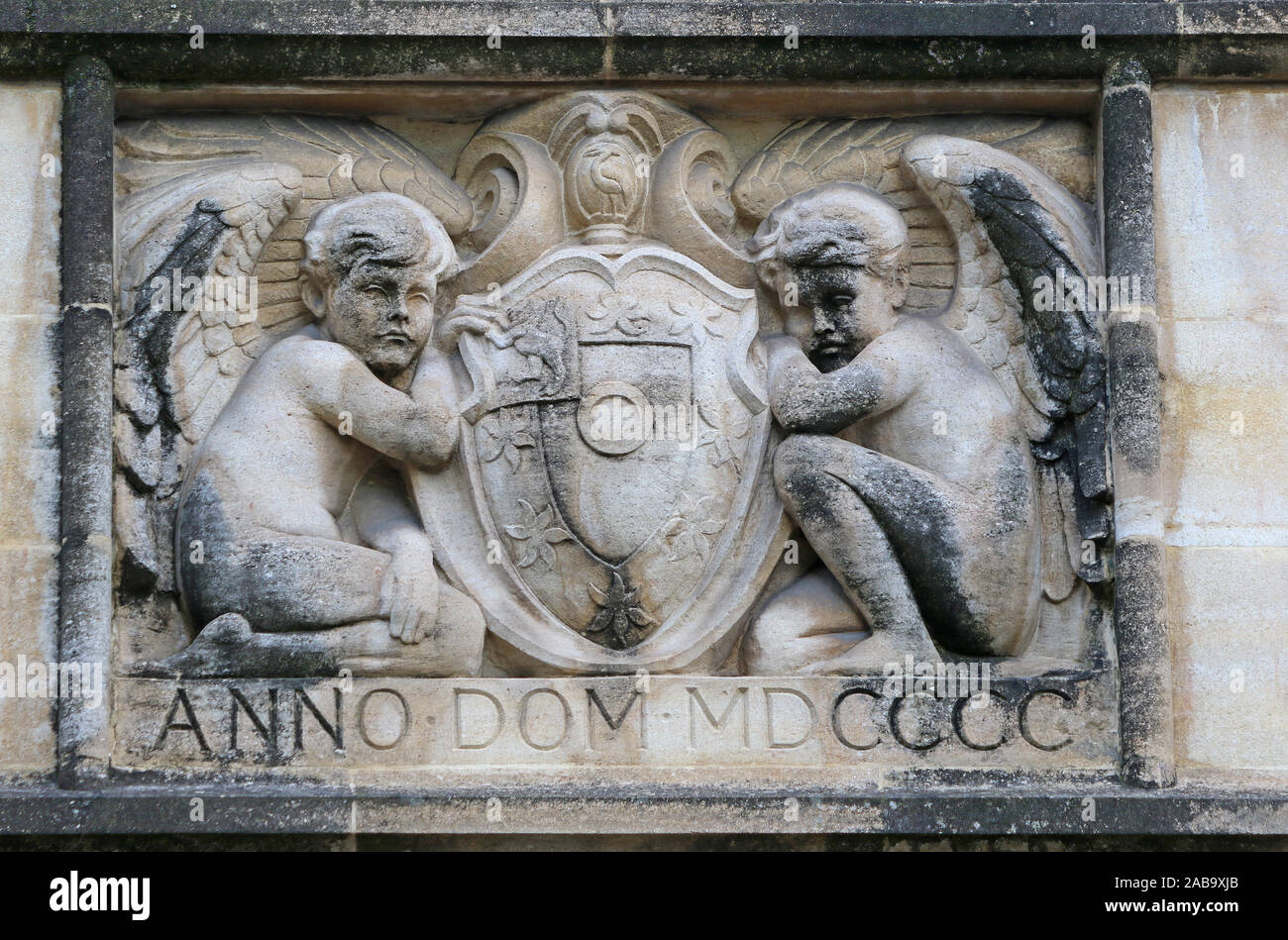 stone carving on a wall in St John's college Oxford part of the university showing two angels or cherubs and the coat of arms of the college from 1900 Stock Photo