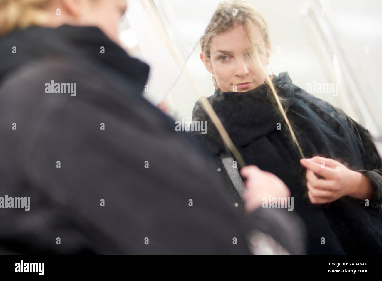 young woman with strand of hair in front of mirror Stock Photo