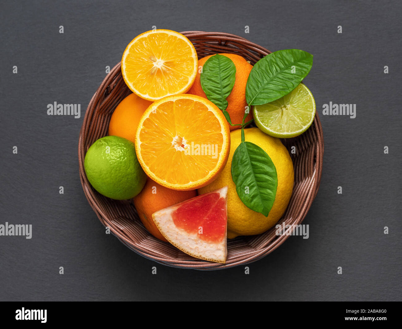 Sliced citrus in a basket on a stone table. Flat lay. Juicy ripe slices of orange, lemon, grapefruit and lime on black background. Fruit mix, top view Stock Photo