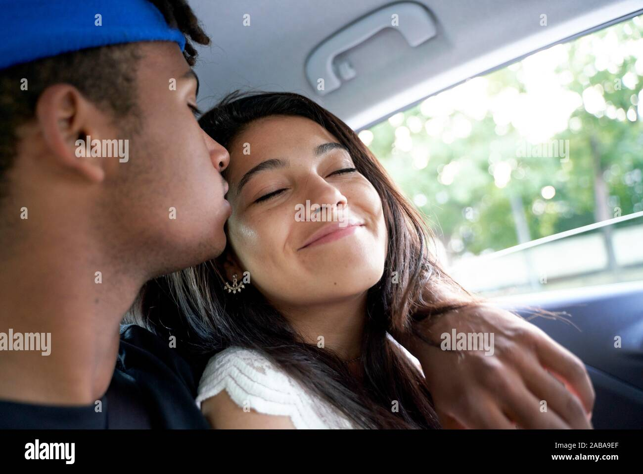 Young couple sitting together in the back seat of car. Stock Photo