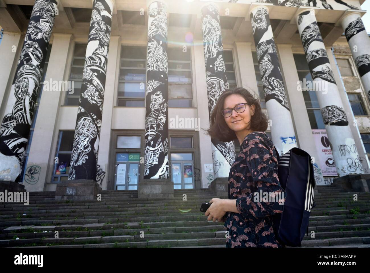 young woman posing in front of the columns of former disused palace of the Soviet period on Tauras Hill, Vilnius, Lithuania, Europe. Stock Photo