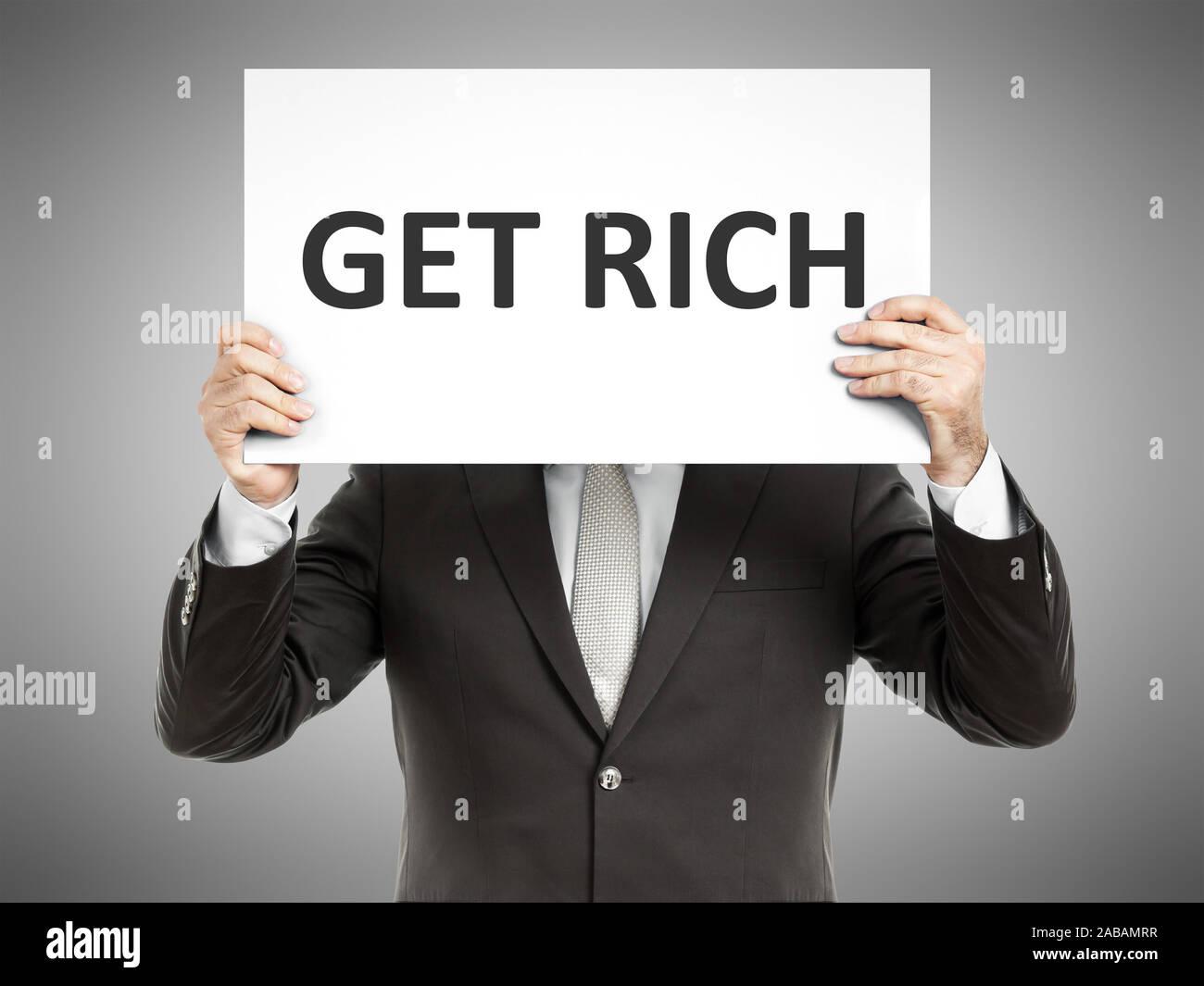 """Ein Geschaeftsmann, der ein Schild mit den Worten """"Get Rich"""" in der Hand haelt Stock Photo"""