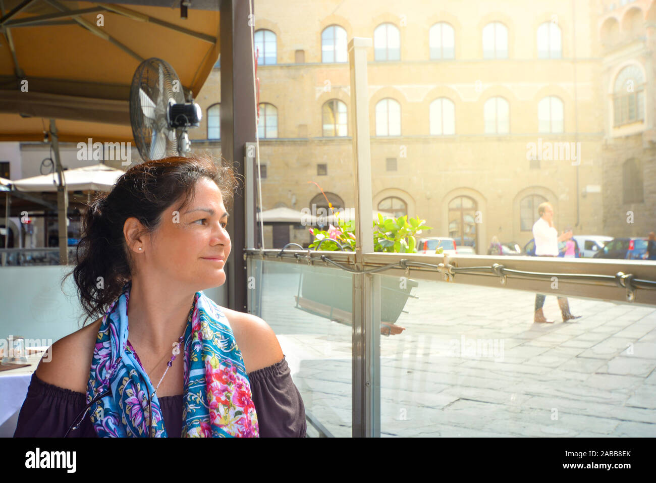 A thirty something attractive brunette gazes with appreciation at her surroundings at a sidewalk cafe in Florence, Italy Stock Photo