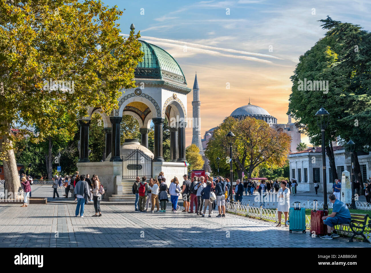 Tourists pass by the German Fountain, a gazebo styled fountain in Sultanahmet Square with the Hagia Sophia in the distance. Stock Photo