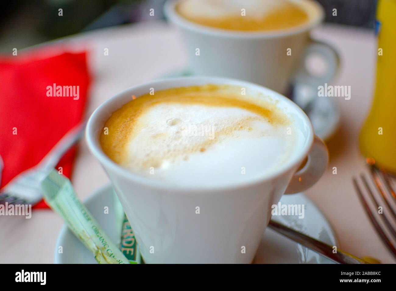 Close up of a table setting with two cups of coffee or cappuccino with milk froth on top. Stock Photo